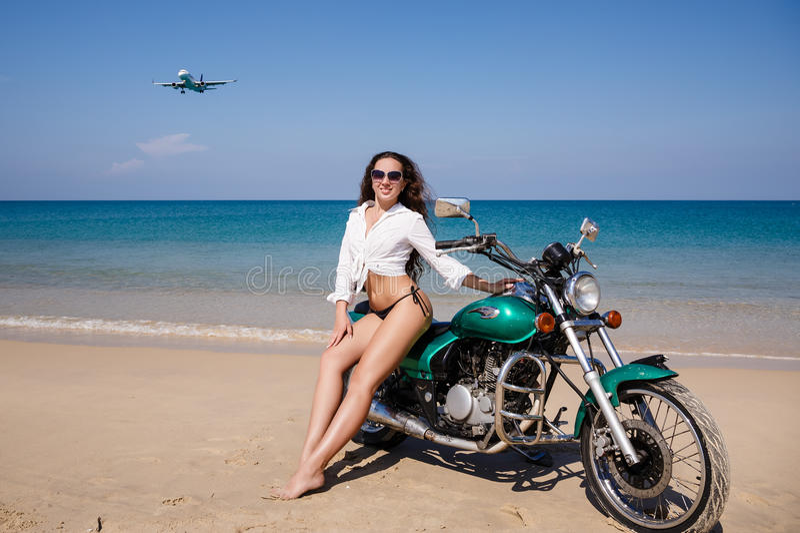 Novo, sexual, a menina na motocicleta, o plano do voo, sobre foto de stock royalty free