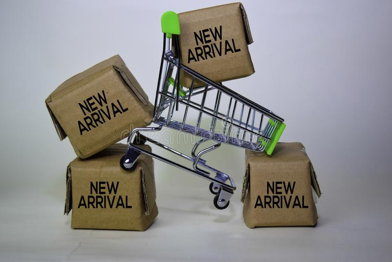 Novo texto de chegada em caixas pequenas e carrinho de compras Conceitos sobre compras online Isolado sobre fundo branco imagem de stock