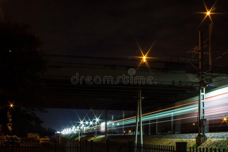Novogireevo järnvägsstation i Moskva Ryssland med ett drev som passerar under vägbron på natten royaltyfria foton