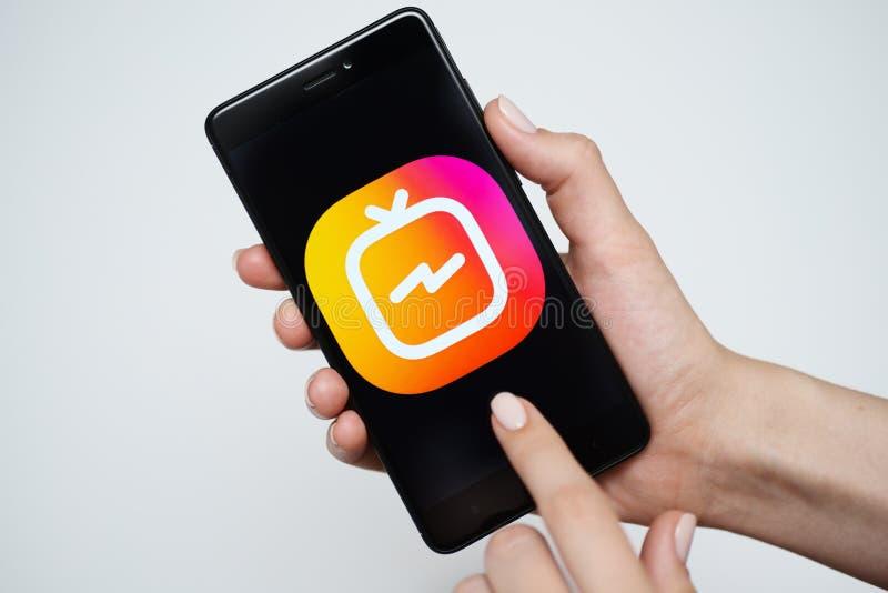 NOVOKUZNETS, RÚSSIA - 24 de junho de 2018: Mulher que guarda um telefone com logotipo de Instagram IGTV imagem de stock