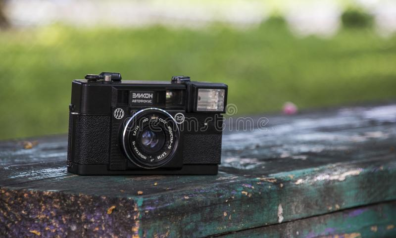 Novopolotsk, Belarus - May 15, 2018: The old camera Elikon. Novopolotsk, Belarus - May 15, 2018: Old camera Elikon is lying on a bench on the background of stock photos