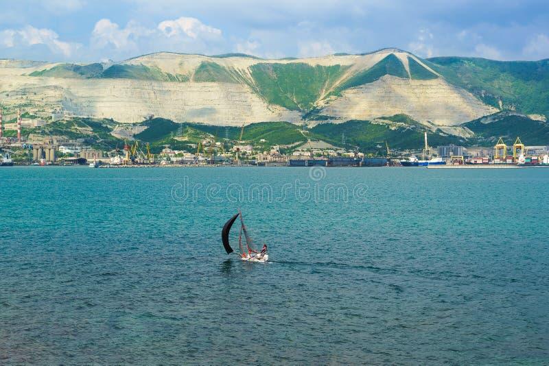 NOVOROSSIYSK, RUSLAND - MEI 08 2016: Sportenzeilboot en panorama van de commerciële zeehaven van Novorossiysk royalty-vrije stock fotografie