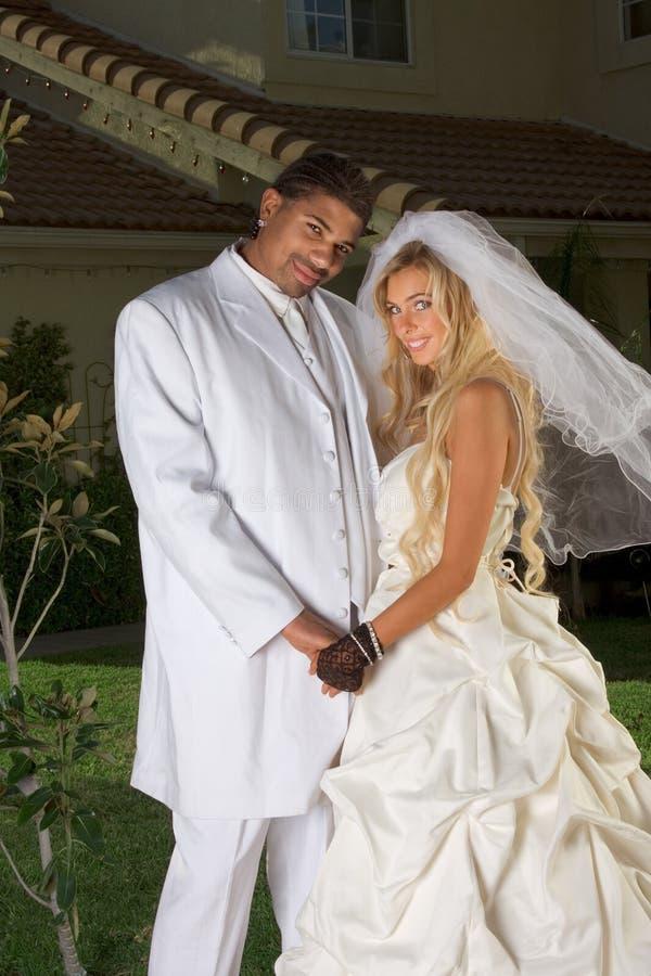 Novos felizes wed pares inter-raciais no modo do casamento fotos de stock