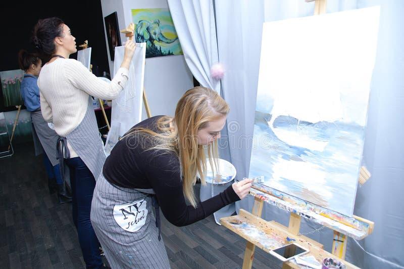 Novosibirsk 02-24-2018 Art Workshop Les filles écrivent à des peintures la peinture acrylique sur la toile photographie stock