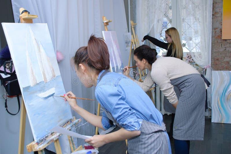 Novosibirsk 02-24-2018 Ocupação na oficina da arte As meninas pintam imagens com pintura acrílica na lona fotografia de stock royalty free
