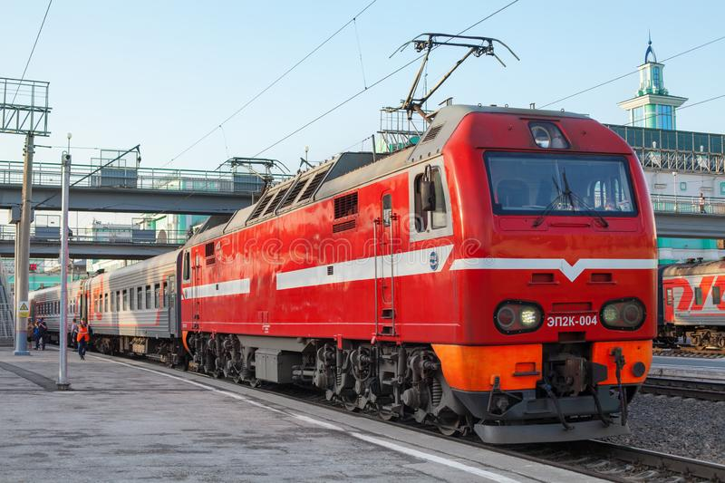 City railway station, passenger train wagons on platform close up, red electric locomotive on tracks, railroad transportation stock photography