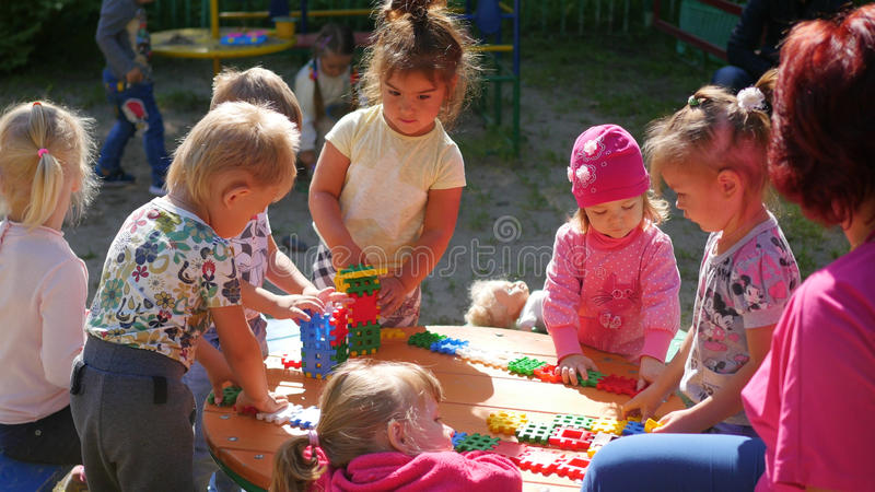 NOVOSIBIRSK, RUSSIA - August 16, 2017: In kindergarten, the woman playing with the children, active games outdoors royalty free stock image