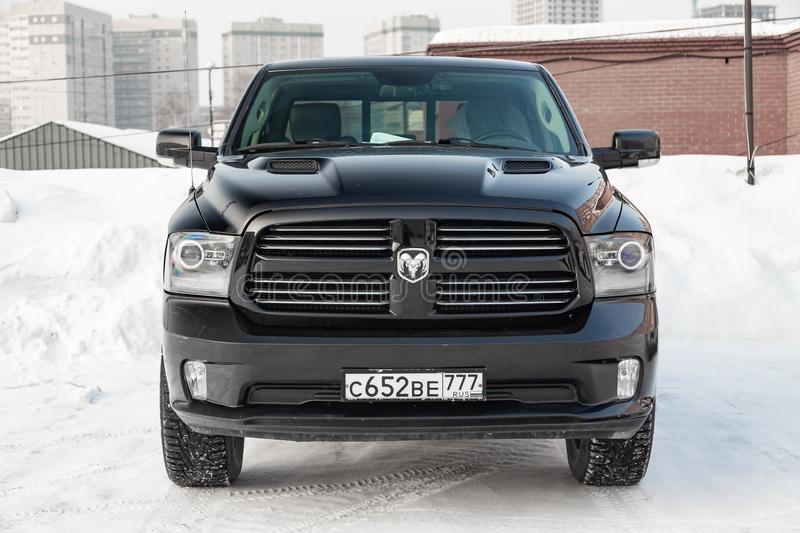 Black Dodge Ram with an engine of 5.7 liters front view on the car parking with snow background stock photography