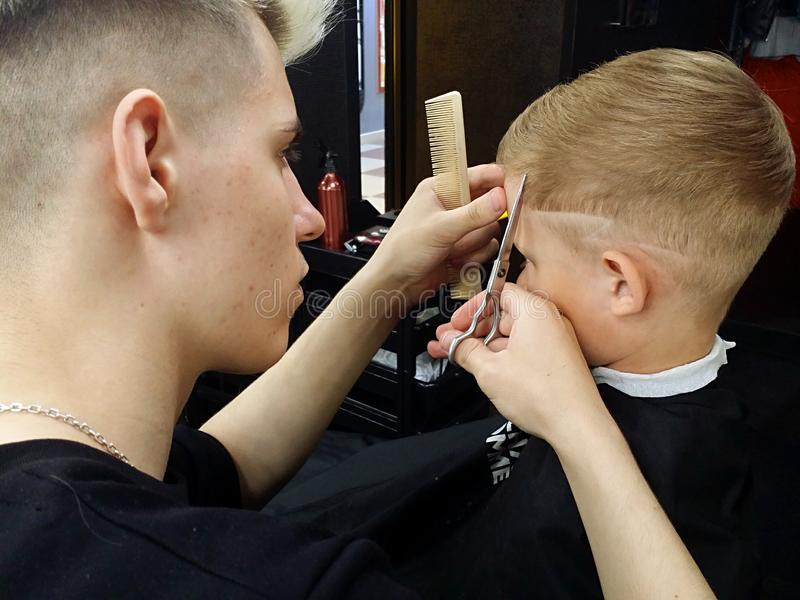 Caucasian hairdresser with scissors and comb cuts the boy in the Barber shop royalty free stock photography