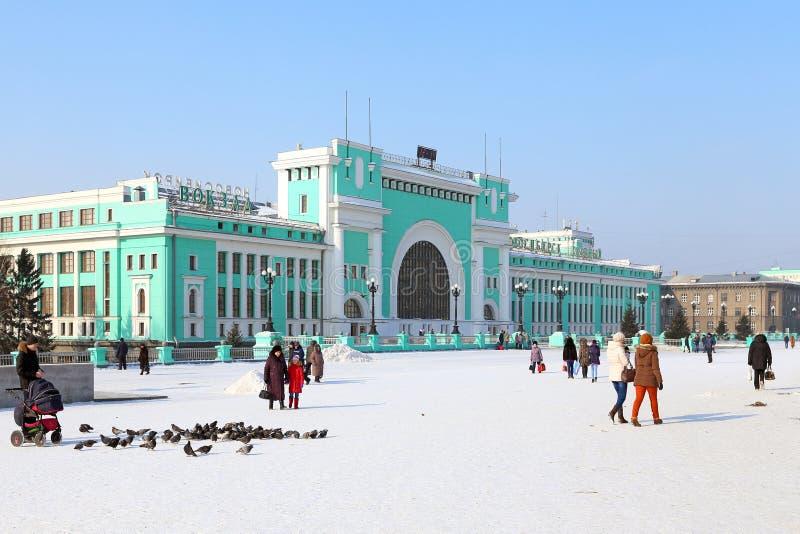 Station square and citizens on a Sunny winter day in Novosibirsk. Novosibirsk, RUSSIA-FEBRUARY 21, 2016: Garin-Mikhailovsky Square and Novosibirsk-Glavny train stock photo