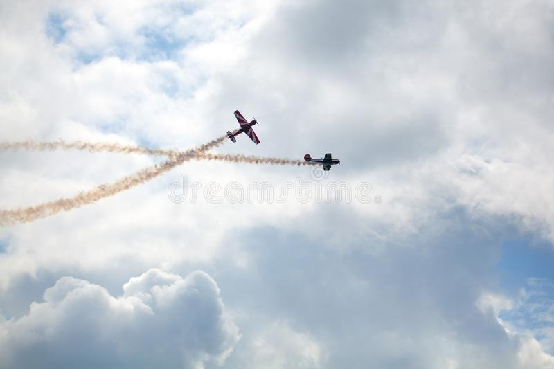 Mochishche airfield, local air show, two Yak-52, aerobatic team `Open Sky`, Barnaul, on blue sky with clouds background stock photos
