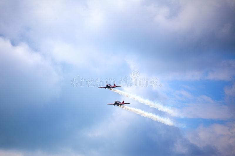Mochishche airfield, local air show, two Yak-52, aerobatic team `Open Sky`, Barnaul, on blue sky with clouds background stock photo
