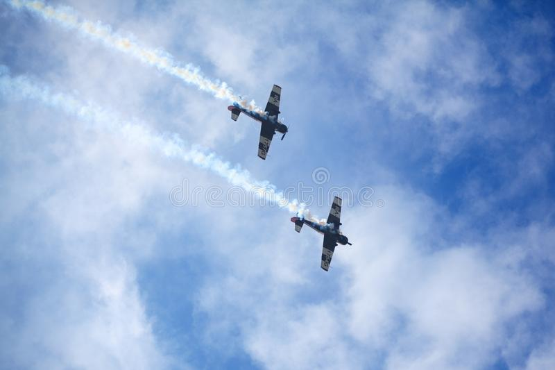 Mochishche airfield, local air show, two Yak-52, aerobatic team `Open Sky`, Barnaul, on blue sky with clouds background stock images