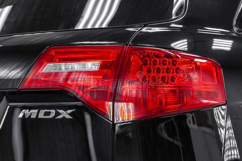 Rear view of used Acura MDX 2008 year black color with red taillamps standing in the light service box of the detailing workshop. Novosibirsk, Russia - 08.01 royalty free stock photo