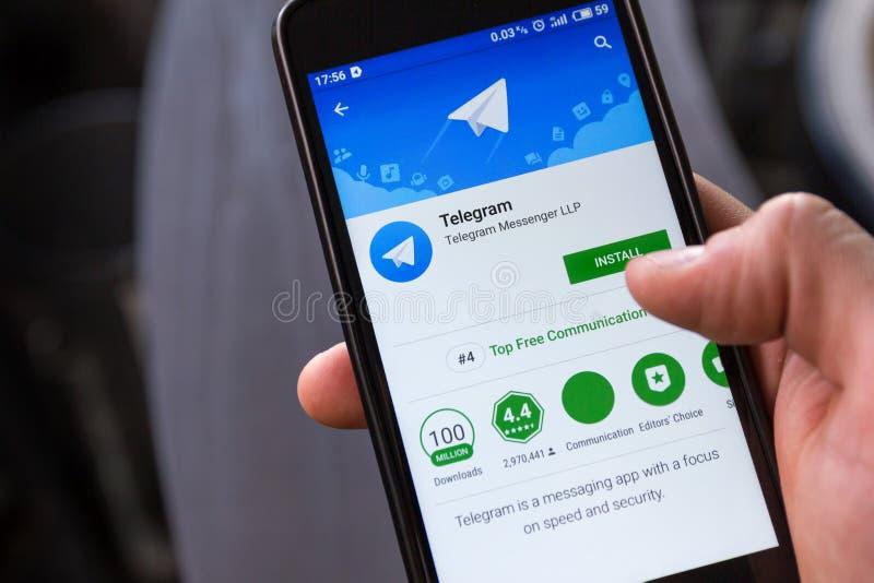 Novosibirsk Ryssland - April 30, 2018 - Smartphone med telegramapplikation i Google leklager på trätabellbakgrund royaltyfri foto