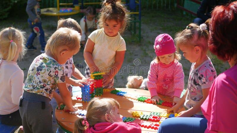 NOVOSIBIRSK RYSSLAND - Augusti 16, 2017: I dagis kvinnan som spelar med barnen, aktiva lekar utomhus royaltyfri bild