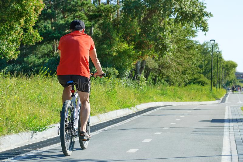 Novosibirsk 07-31-2018 Um homem está montando uma bicicleta no parque imagens de stock royalty free