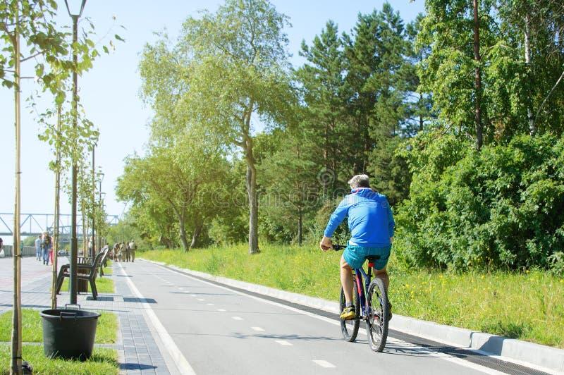 Novosibirsk 07-31-2018 Un homme monte une bicyclette en parc images stock