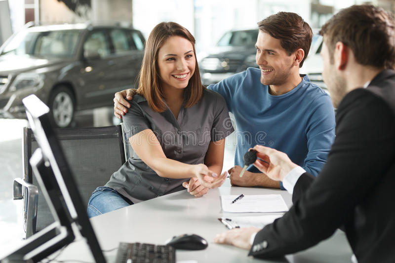 Now her dream comes true. Car salesman giving the key of the new. Car to the young attractive owners stock photo