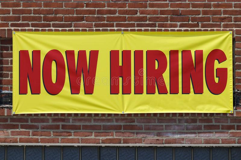 Now Hiring bright yellow banner sign with red print I royalty free stock images