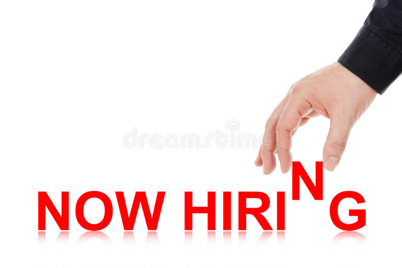 Now hiring. Male hand placing letters to form the words now hiring stock image