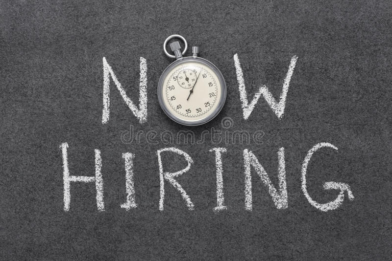 Now hiring. Phrase handwritten on chalkboard with vintage precise stopwatch used instead of O stock photography