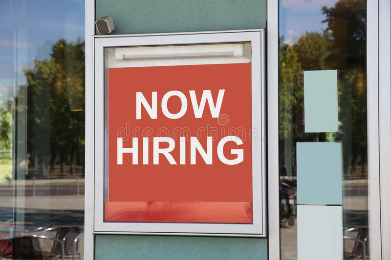 Now hiring sign outside modern office building royalty free stock image