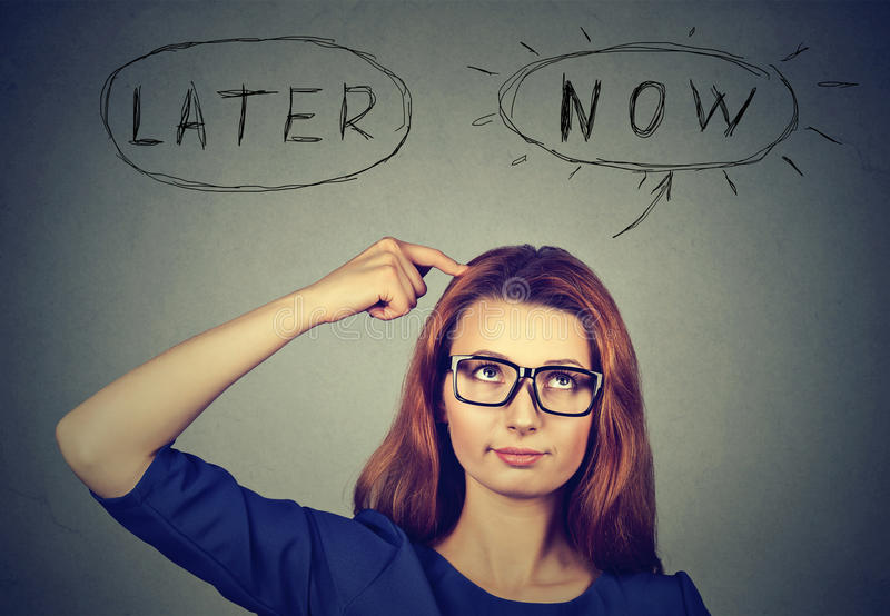 Now or later. Woman thinking looking up. royalty free stock photos