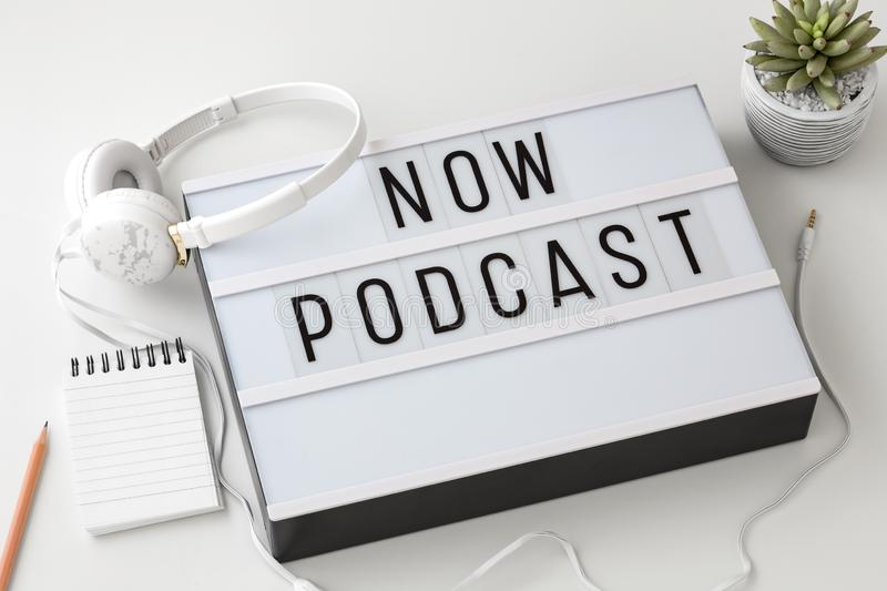 Now Podcast word on lightbox with headphones, podcast concept stock photos