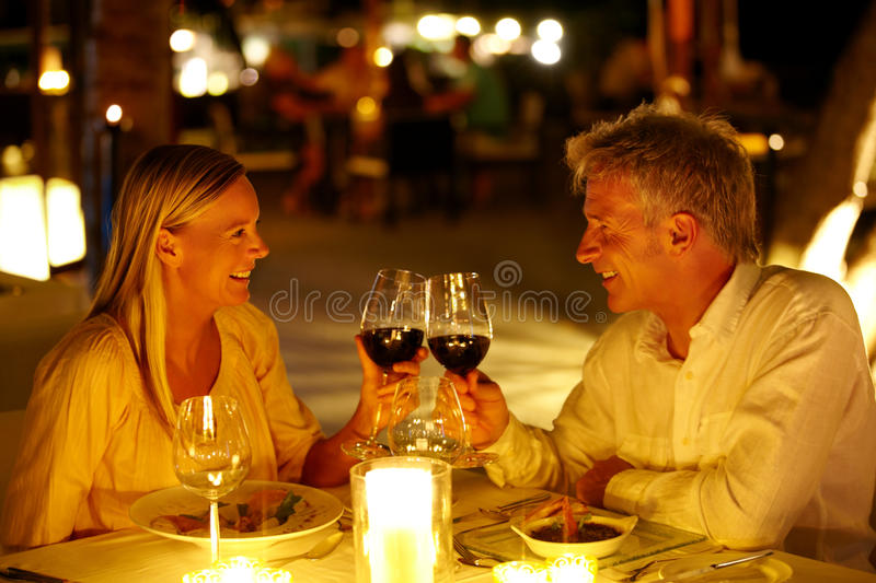 Now that is romantic. Mature couple enjoying candlelight dinner in a restaurant toasting wine glasses