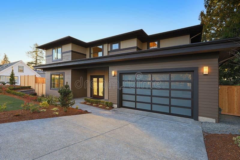Nowa budowa dom z niskim skłonu dachem i brown popierać kogoś obrazy royalty free