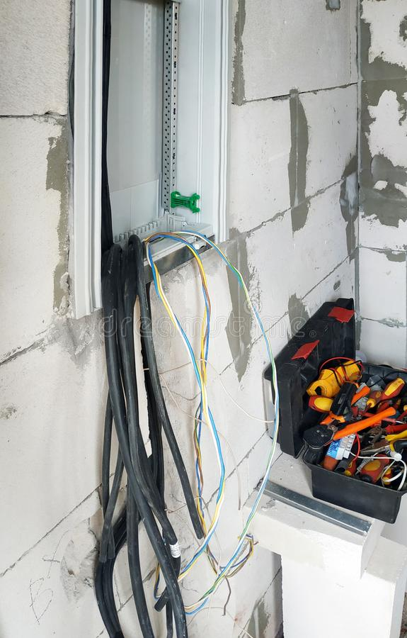 Nowa elektryczna osłona instaluje na ścianie niedawno budujący dom, depeszuje i narzędzia są widoczni obrazy royalty free