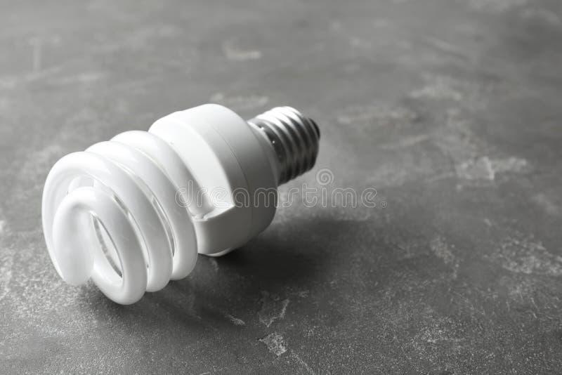 Nowa fluorescencyjna lampowa żarówka na popielatej kamień powierzchni obraz royalty free