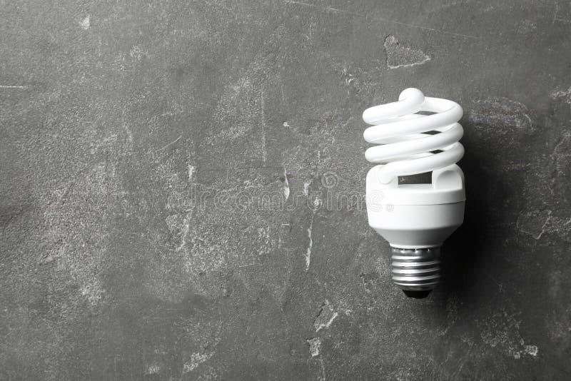 Nowa fluorescencyjna lampowa żarówka na popielatej kamień powierzchni Przestrze? dla teksta zdjęcia stock