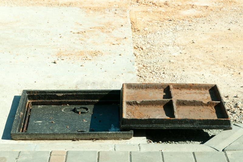 Nowa metal pokrywa nad betonowym manhole przy budowy drogi miejsca zakończeniem up zdjęcia royalty free