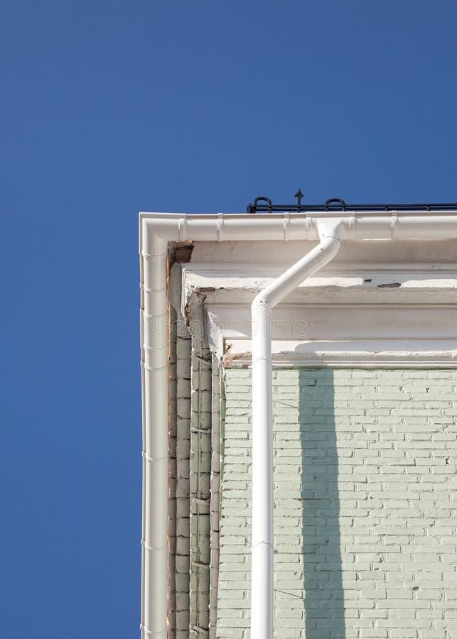 Nowa podeszczowa rynna na ściana z cegieł przeciw niebieskiemu niebu obrazy stock