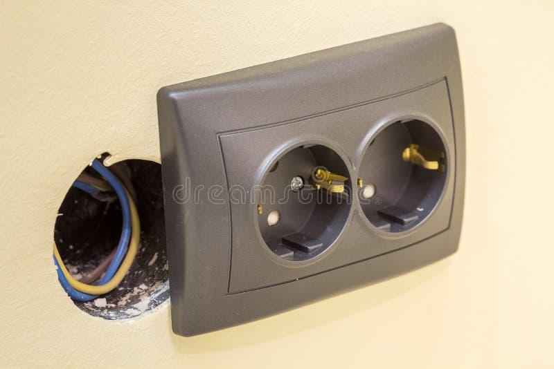 Nowa szarej władzy ujścia nasadka z elektrycznymi odosobnionymi kolorowymi drutami, klingeryt wtyczkowa instalacja na jasnożółtej zdjęcie royalty free