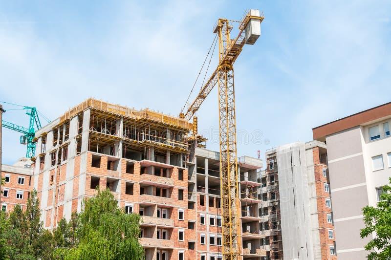 Nowa wysoka budynek mieszkalny budowa w mieście z żurawiami i rusztowaniem, niebieskiego nieba tło fotografia stock