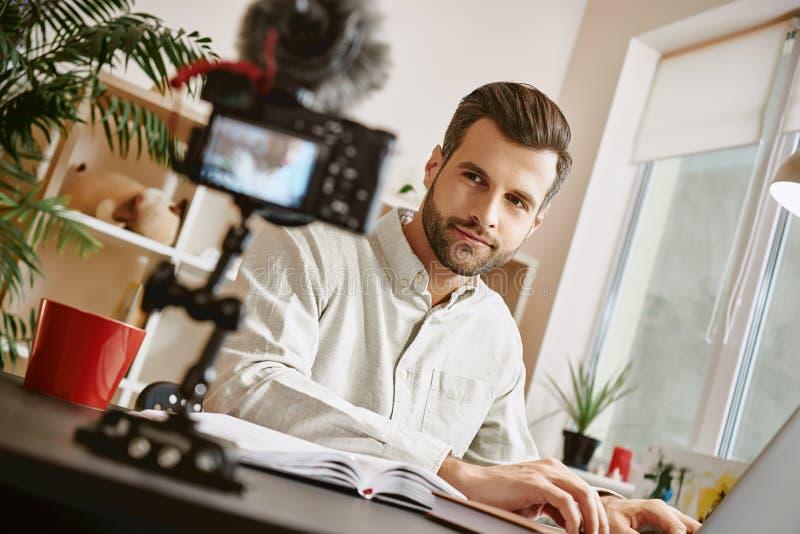 Nowa zawartość Młody męski blogger patrzeje kamerę, uśmiecha się nowego wideo i nagrywa, podczas gdy siedzący indoors zdjęcia stock