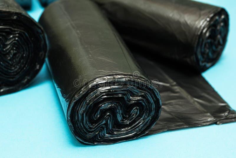 Nowe czarne torby na śmiecie na błękitnym tle zdjęcie royalty free