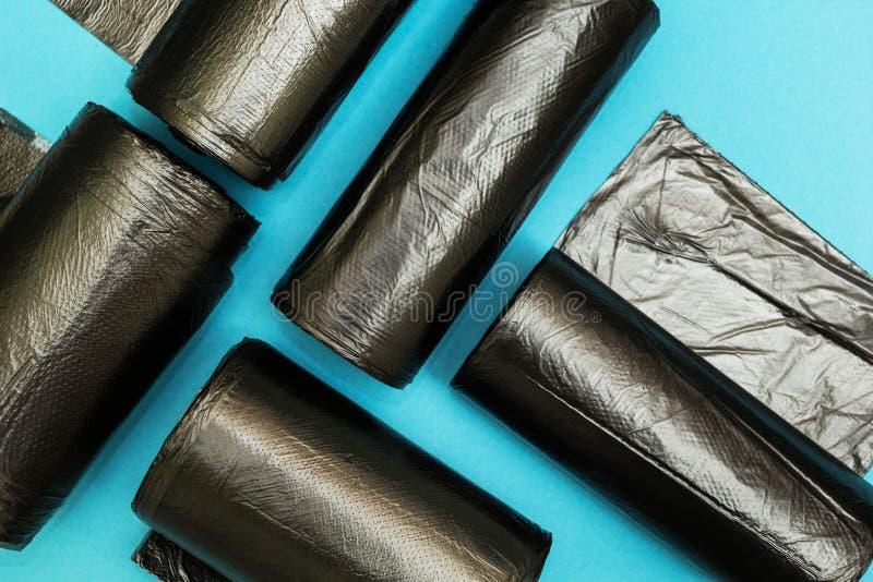 Nowe czarne torby na ?miecie na b??kitnym tle fotografia royalty free