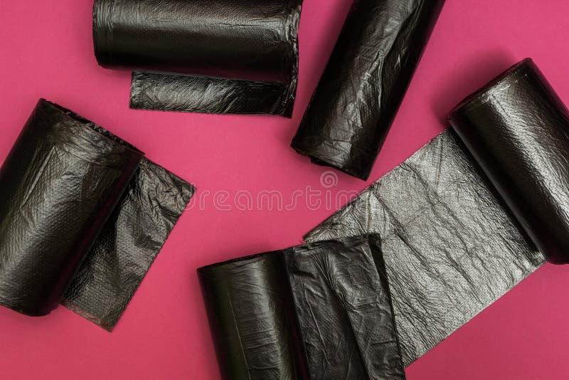 Nowe czarne torby na ?miecie na r??owym tle obrazy stock