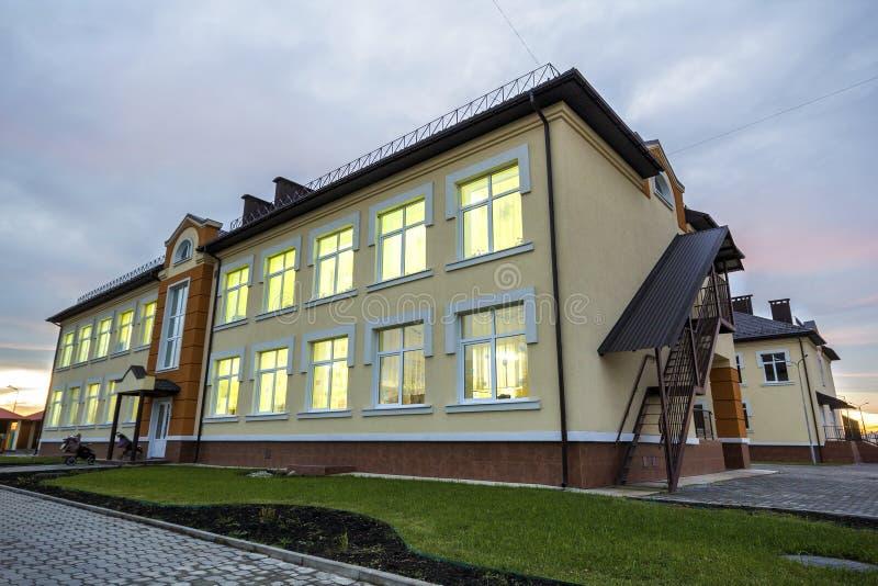 Nowego nowożytnego jednopiętrowego dziecina preschool budynek, zielony trawiasty gazon i brukujący chodniczki na niebieskie niebo obrazy stock