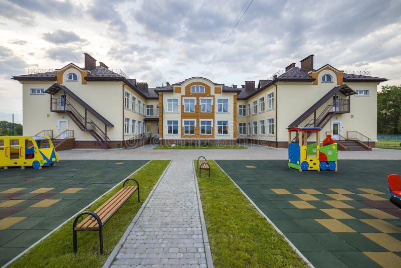 Nowego nowożytnego jednopiętrowego dziecina preschool budynek z dużymi okno na zielonej trawiastej gazonu i niebieskiego nieba ko zdjęcie royalty free