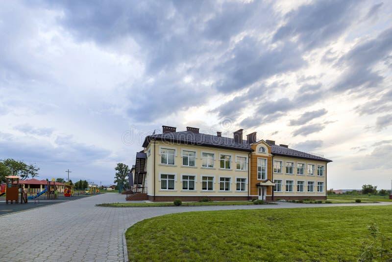Nowego nowożytnego jednopiętrowego dziecina preschool budynek z dużymi okno na zielonej trawiastej gazonu i niebieskiego nieba ko zdjęcie stock