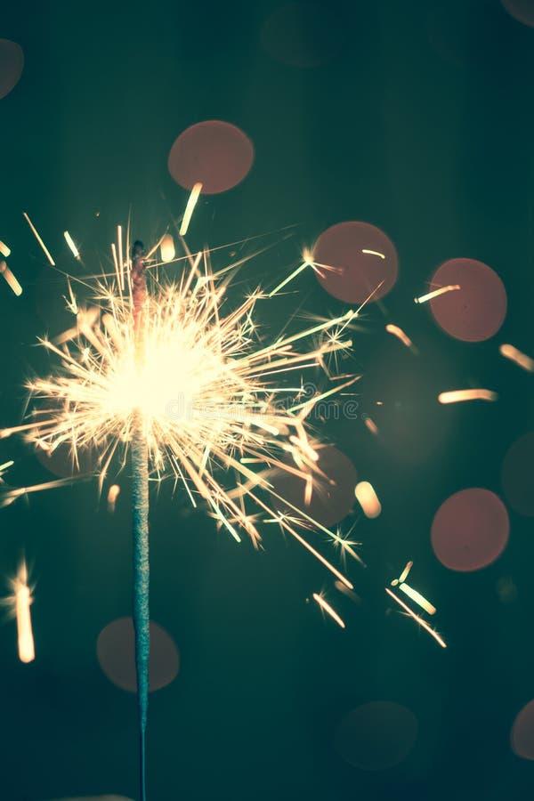Nowego Roku Bożenarodzeniowy sparkler na ciemnym tle z bokeh zaświeca obrazy stock