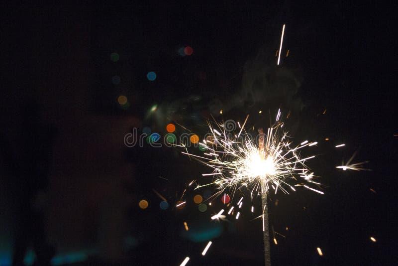 Nowego Roku Bożenarodzeniowy sparkler na ciemnym tle z bokeh zaświeca zdjęcie royalty free