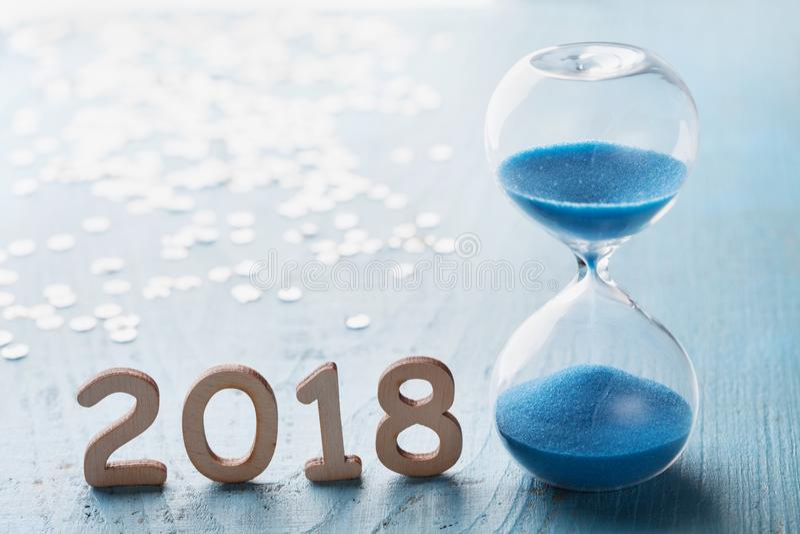 Nowego roku 2018 kartka z pozdrowieniami Hourglass lub sandglass na błękitnym drewnianym stole fotografia stock