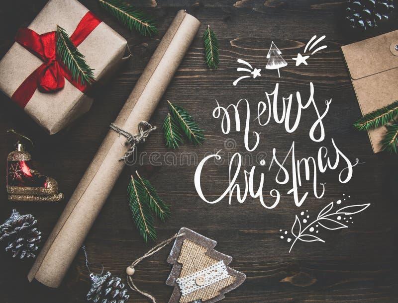 Nowego Roku koncert, zawijający prezent, opakunkowy papier, choinek gałąź i zabawki na drewnianym nieociosanym tle, zdjęcie royalty free