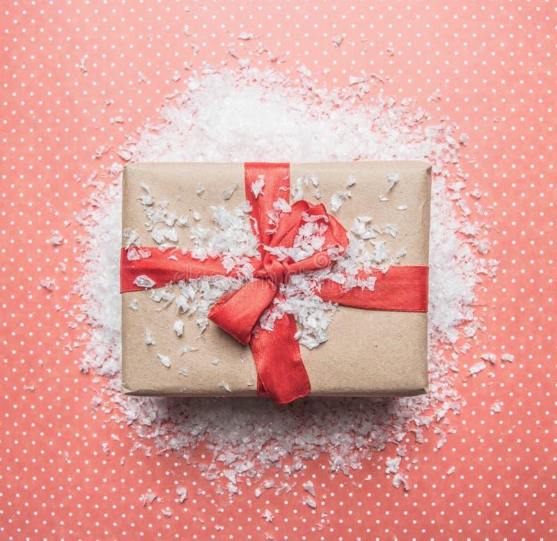 Nowego Roku pojęcie, pudełko z prezentem, choinek zabawki rozkłada na różowym tle z śnieżnym mieszkaniem nieatutowym obrazy stock